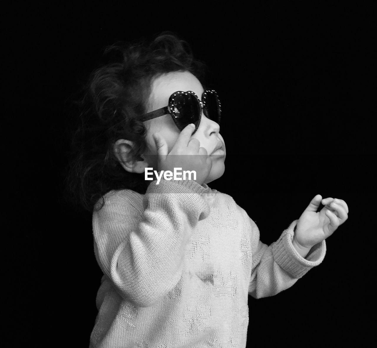 Girl Wearing Sunglasses Against Black Background