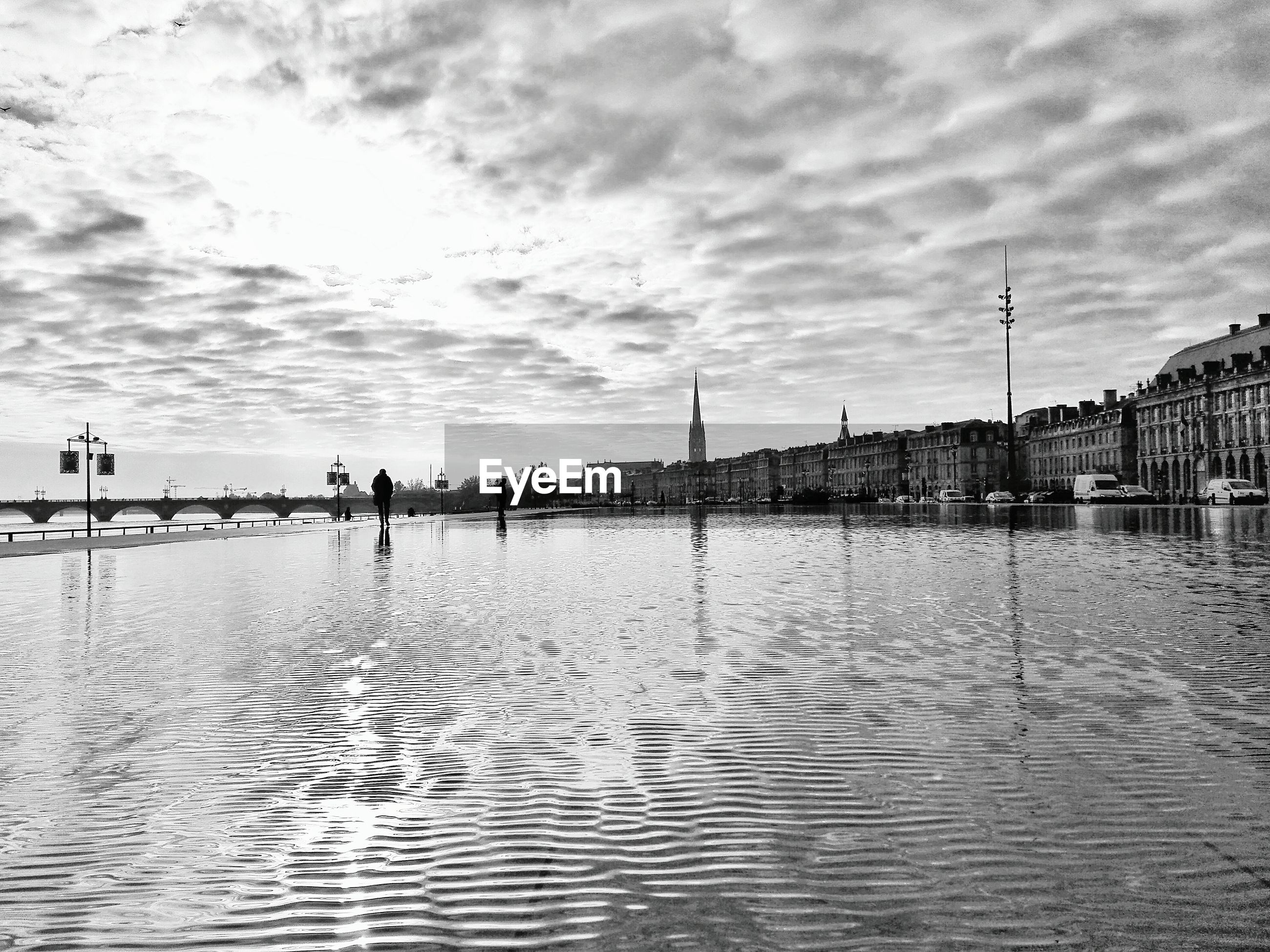 City by garonne river against cloudy sky