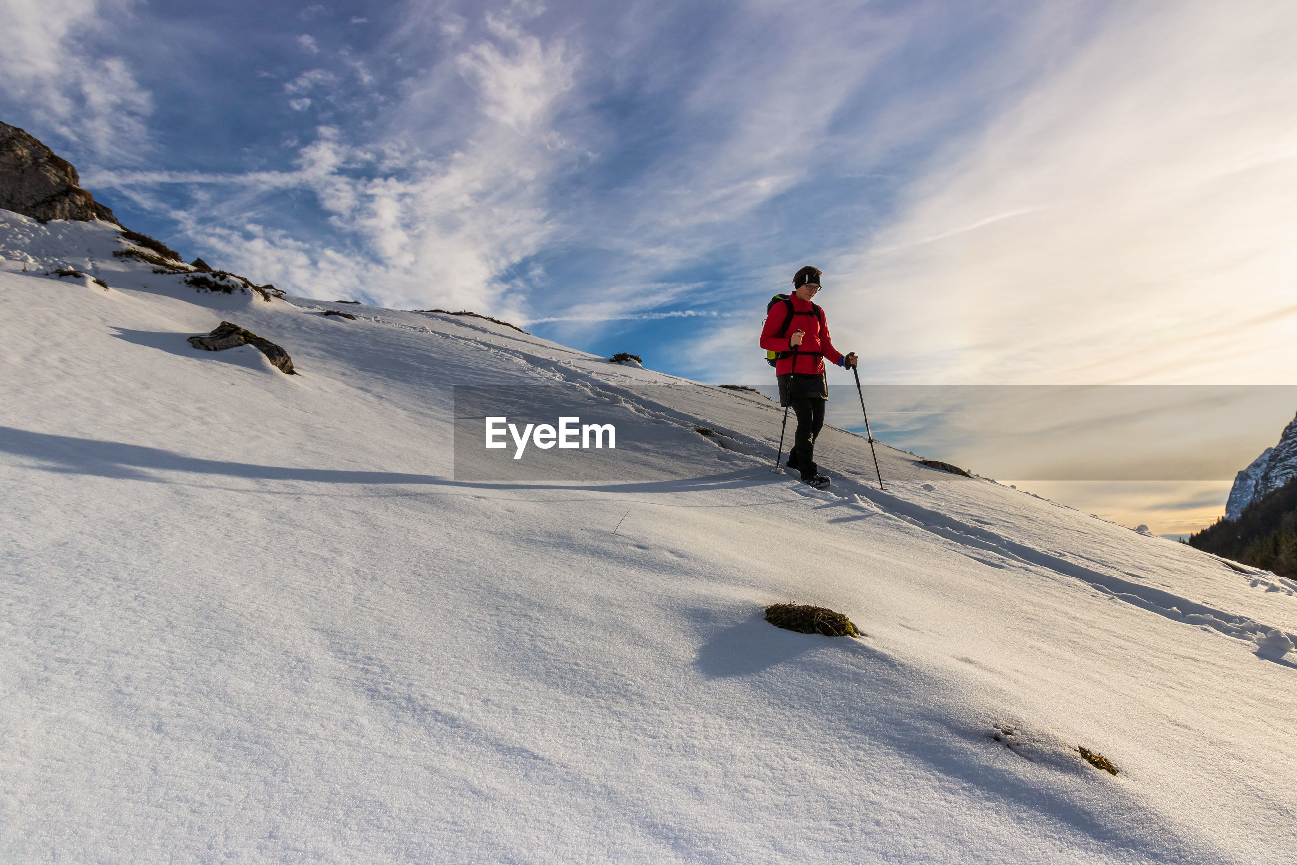 Low angle view of person hiking on snow covered land