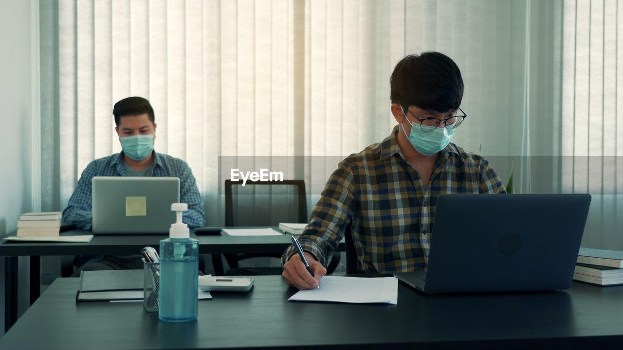Businessmen wearing mask working in office