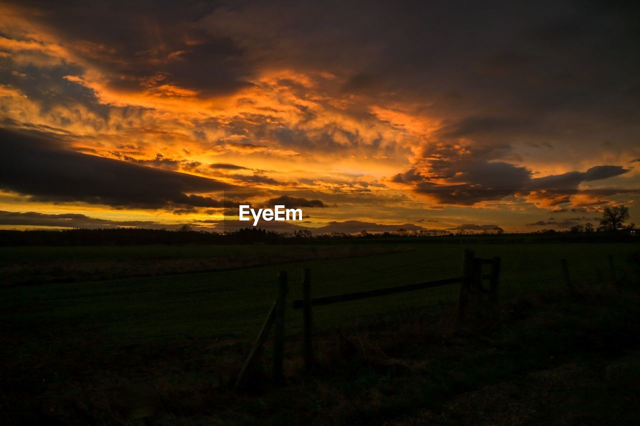 sunset, sky, cloud - sky, beauty in nature, tranquil scene, scenics - nature, field, tranquility, land, landscape, environment, no people, nature, idyllic, orange color, grass, rural scene, fence, barrier, boundary, outdoors