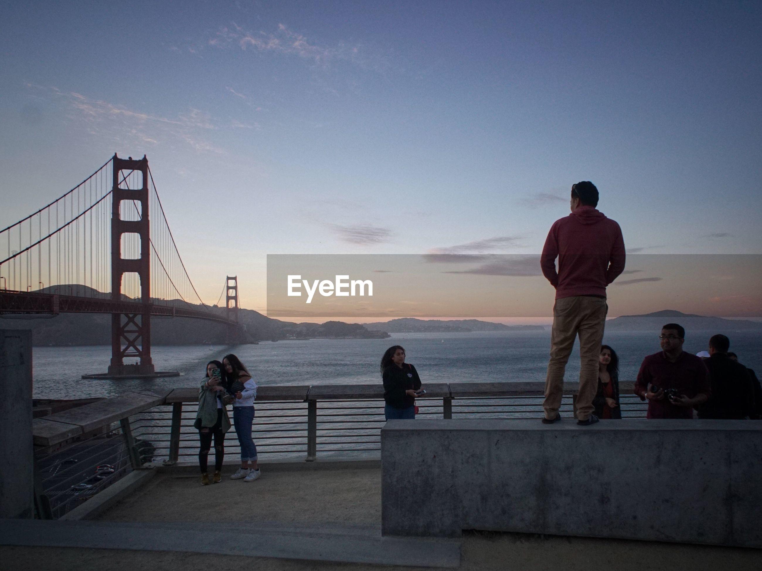 PEOPLE ON SUSPENSION BRIDGE OVER SEA