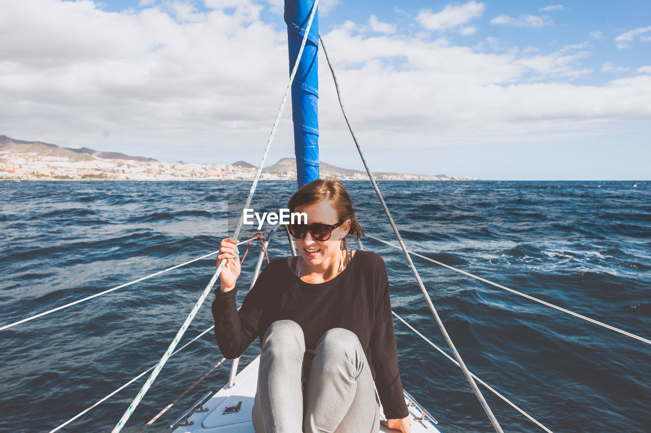 Smiling Young Woman Sitting In Boat On Sea
