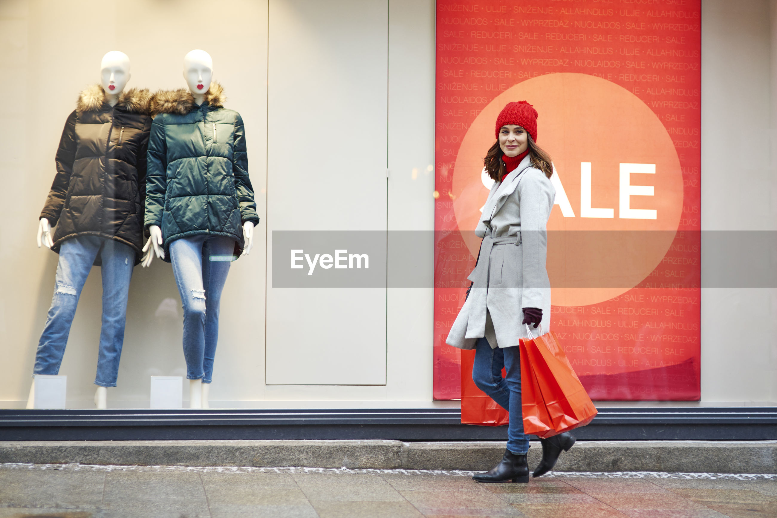 Portrait of woman holding shopping bags against store in city during winter