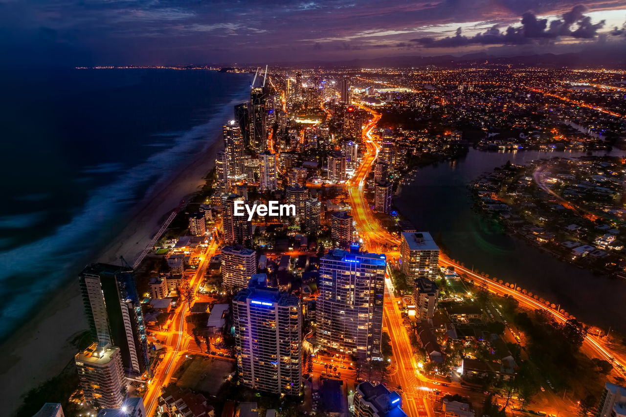 building exterior, city, architecture, cityscape, illuminated, built structure, high angle view, night, water, sky, building, residential district, nature, cloud - sky, sea, dusk, no people, city life, office building exterior, outdoors, skyscraper, modern, nightlife