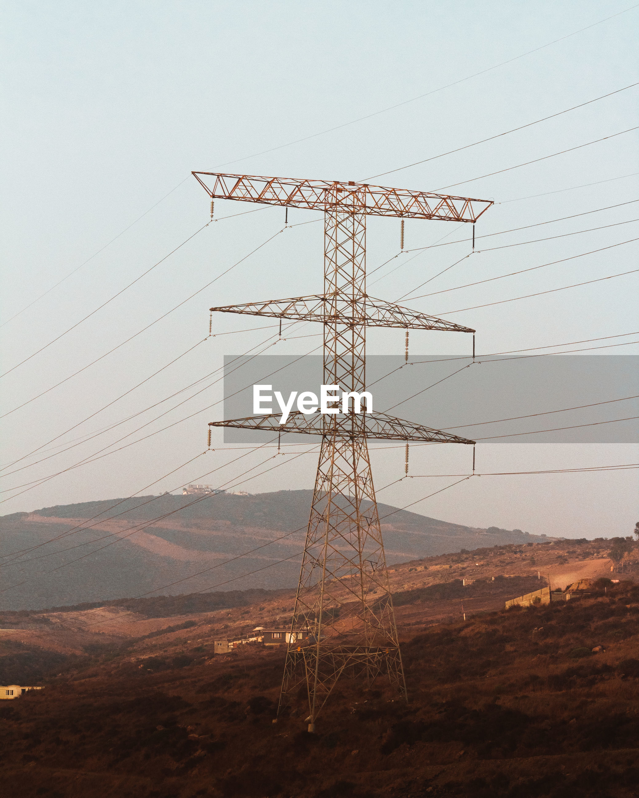LOW ANGLE VIEW OF ELECTRICITY PYLONS ON FIELD AGAINST SKY
