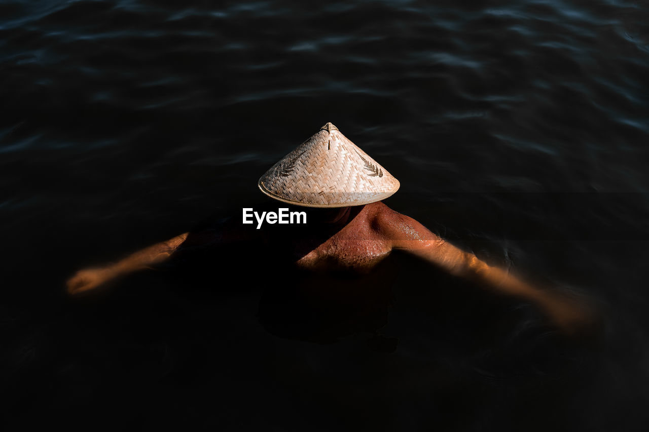 High Angle View Of Man Wearing Asian Style Conical Hat While Swimming In Sea