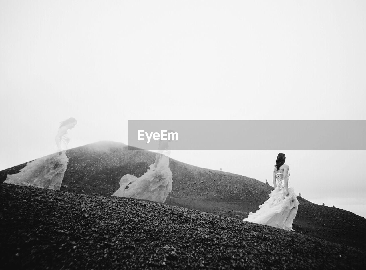Multiple image of woman walking on mountain against clear sky
