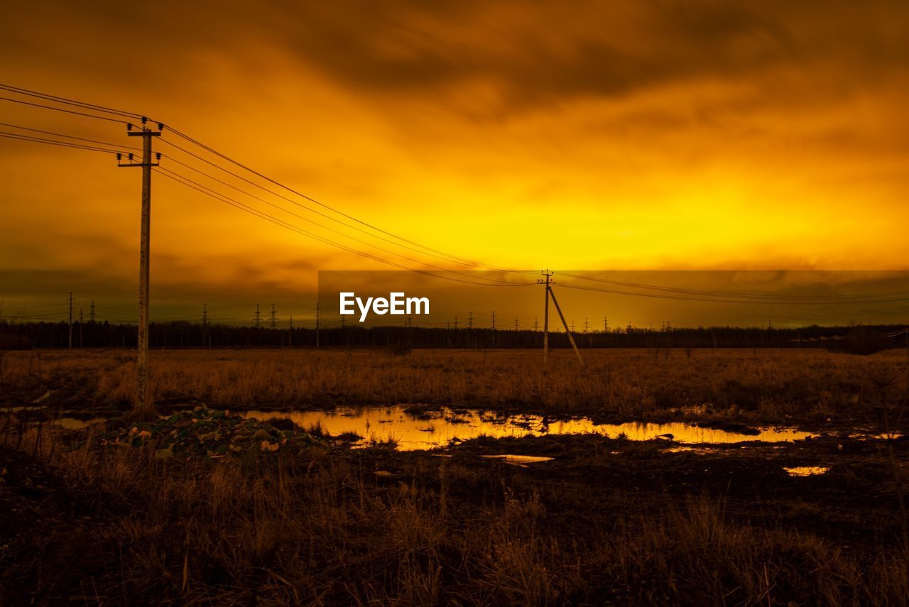 ELECTRICITY PYLON ON FIELD AGAINST ORANGE SKY