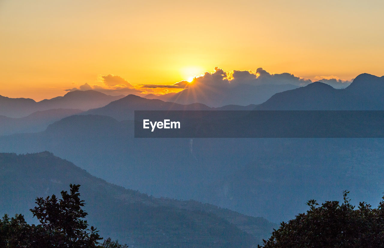 mountain, sky, sunset, scenics - nature, beauty in nature, tranquil scene, tranquility, mountain range, tree, plant, non-urban scene, idyllic, orange color, nature, silhouette, no people, environment, sun, landscape, outdoors, mountain peak