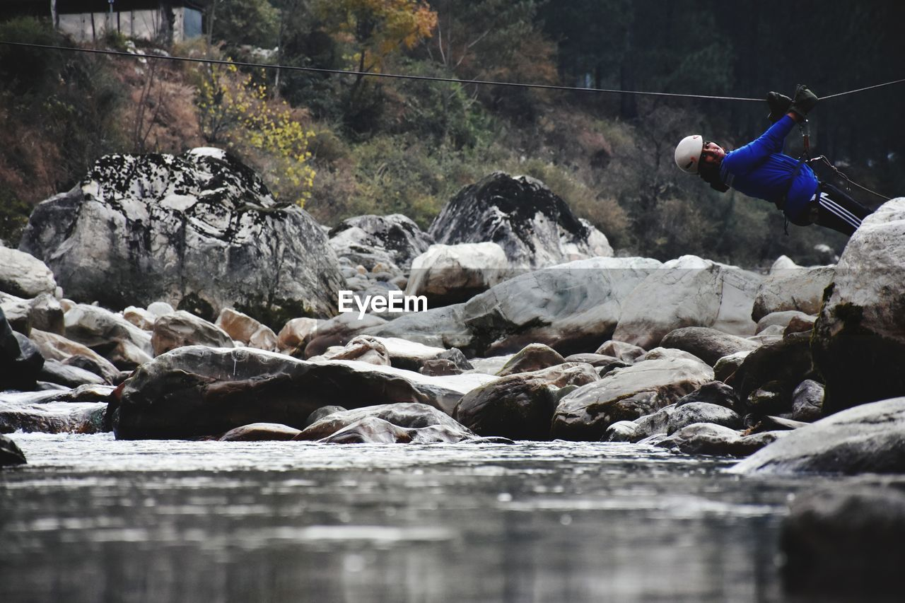 real people, water, rock, solid, day, nature, rock - object, tree, one person, forest, motion, lifestyles, river, leisure activity, waterfall, outdoors, waterfront, flowing water, flowing