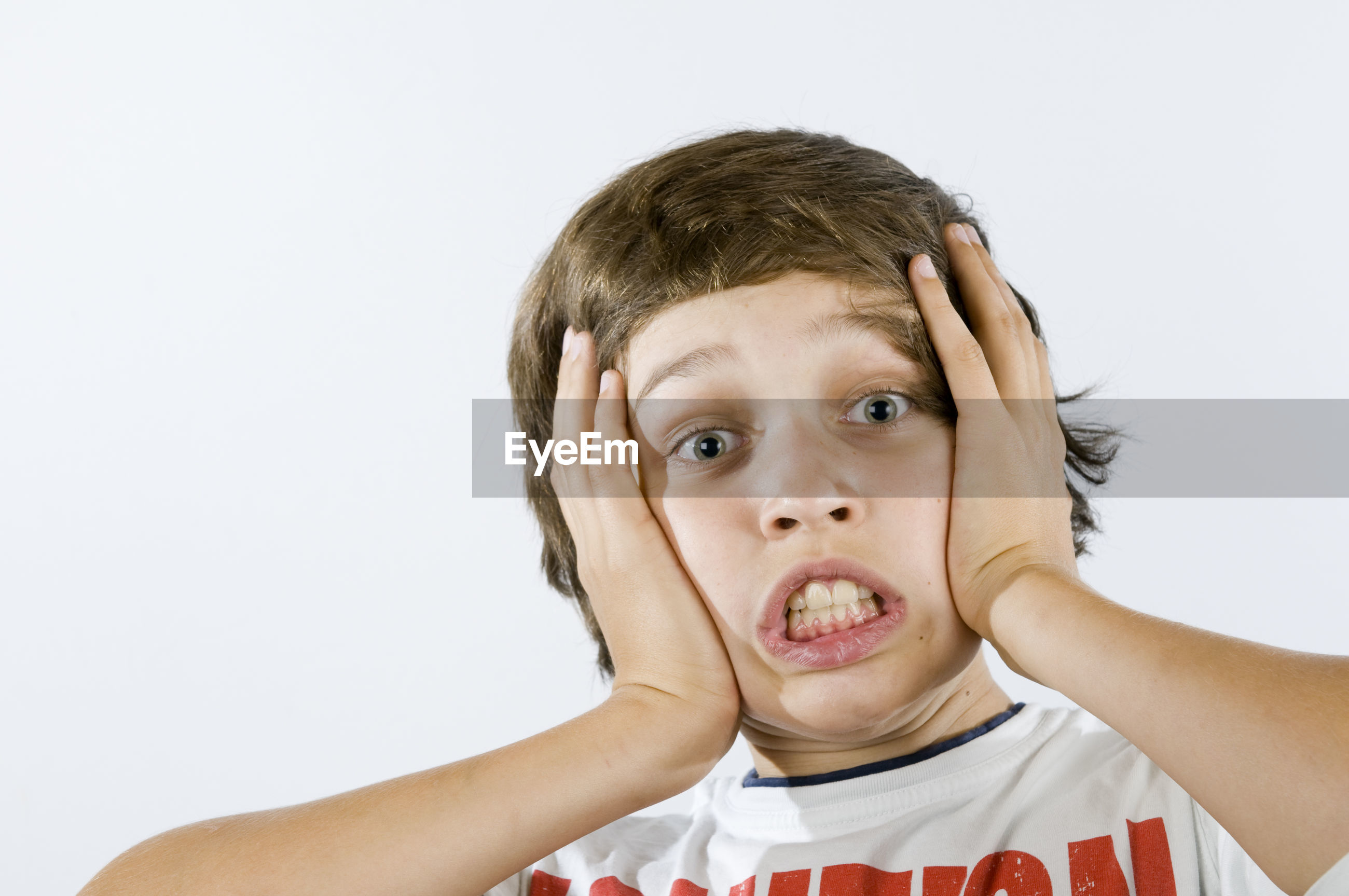 Portrait of grimacing boy with head in hands against white background