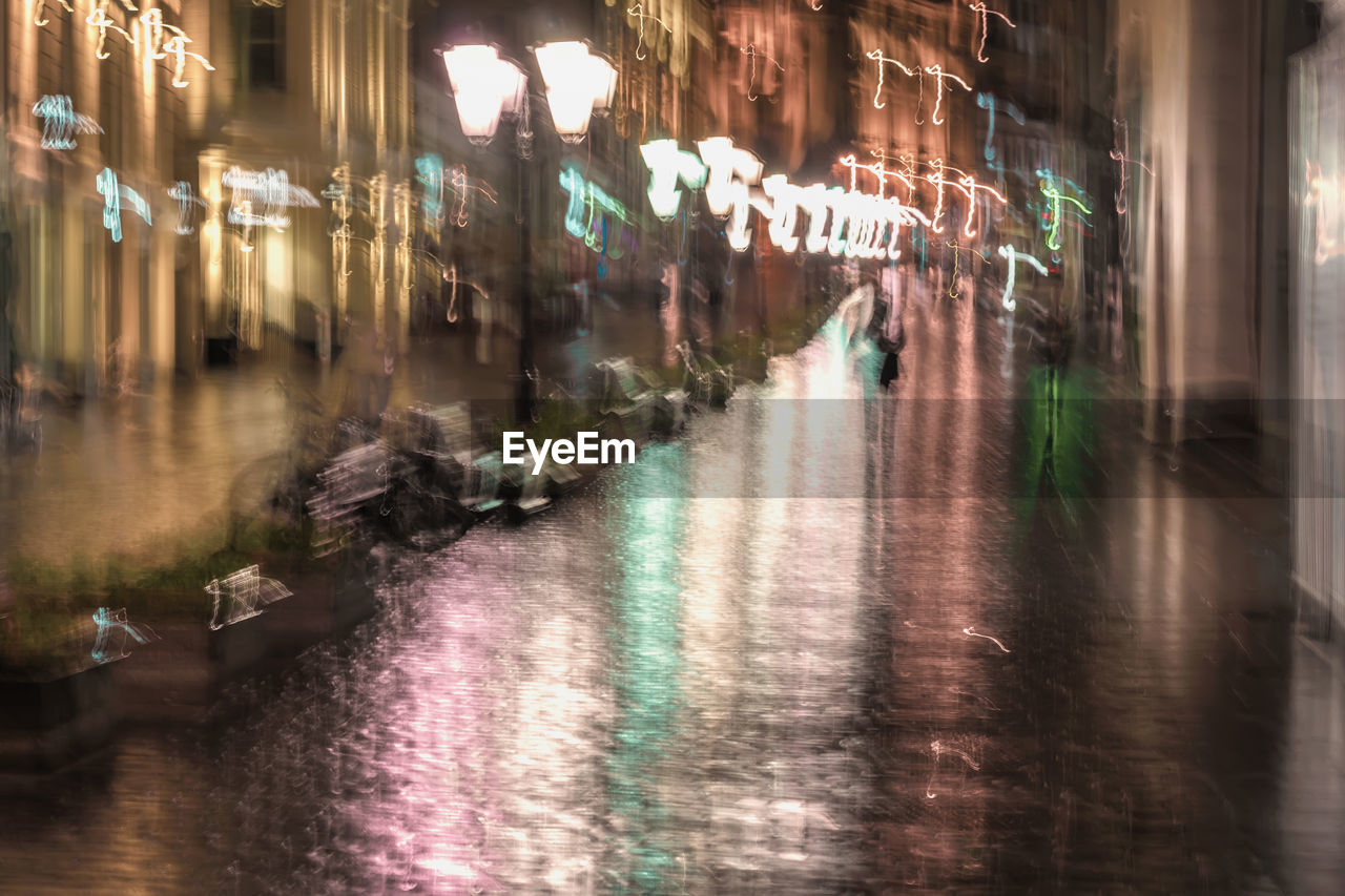 night, illuminated, building exterior, architecture, city, street, reflection, built structure, water, motion, blurred motion, direction, wet, transportation, rain, incidental people, the way forward, long exposure, outdoors, rainy season