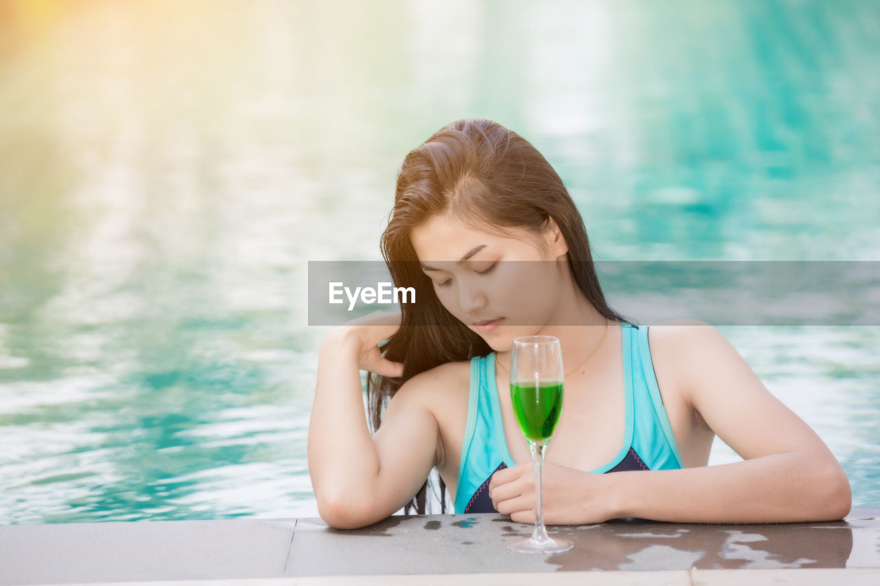 Beautiful woman with drink at poolside