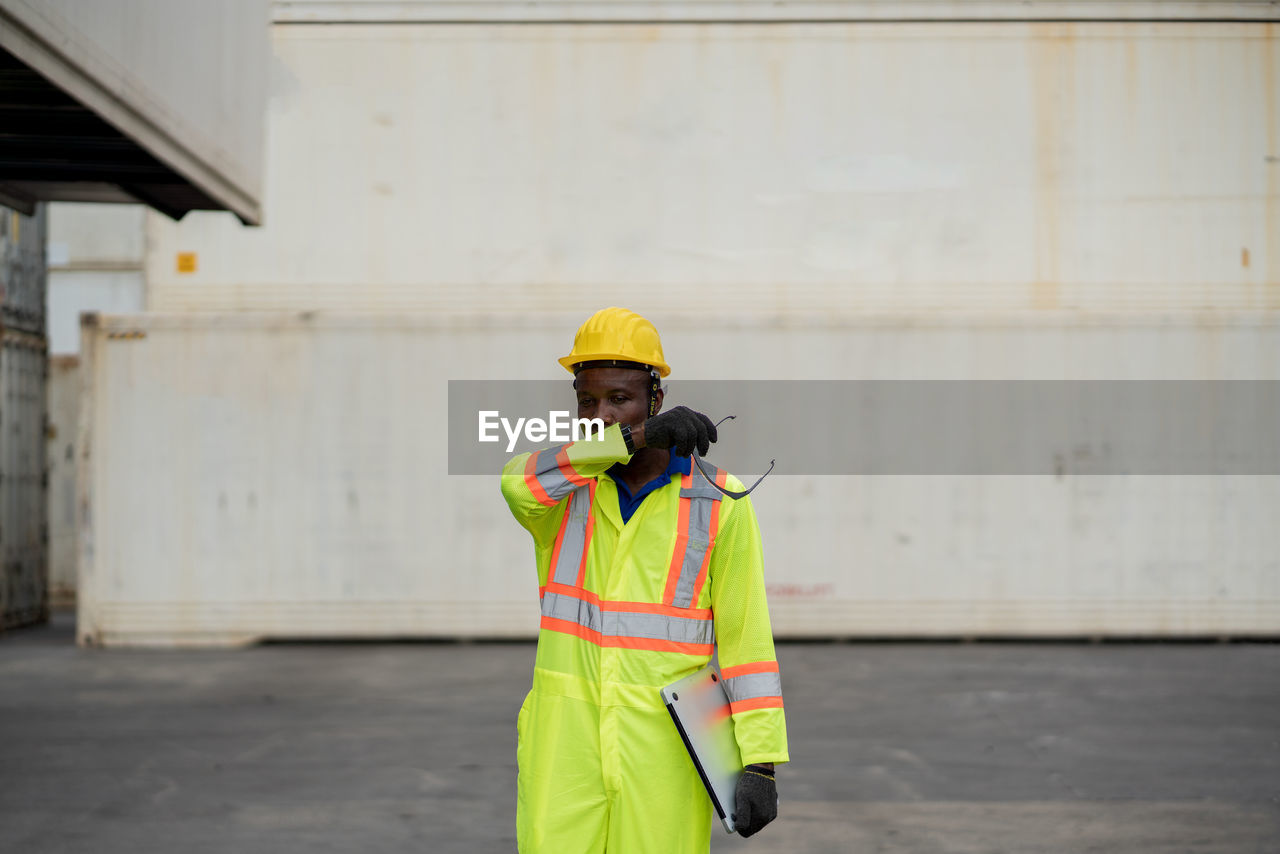 MAN WORKING WITH UMBRELLA STANDING IN FRONT OF BUILT STRUCTURES