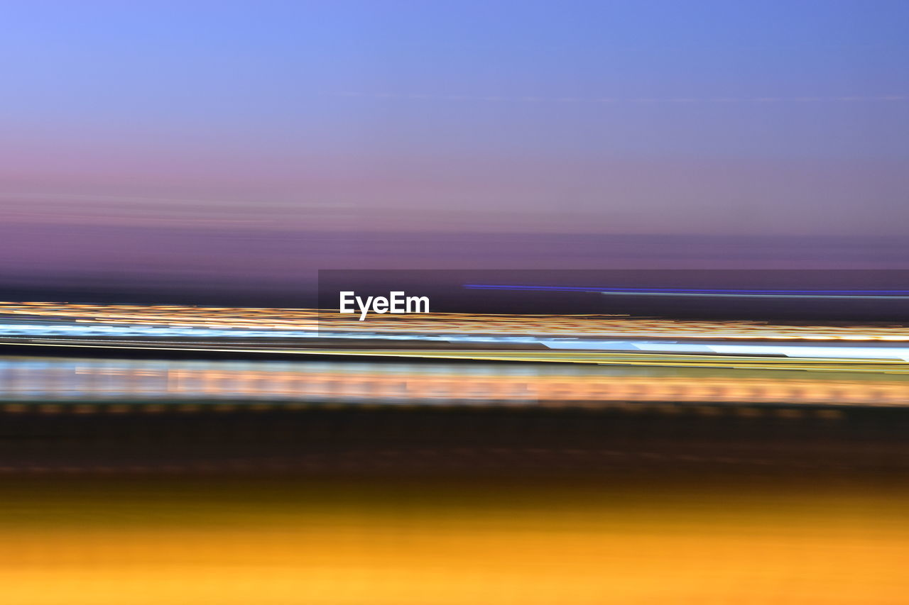 LIGHT TRAILS IN SEA AGAINST SKY AT SUNSET