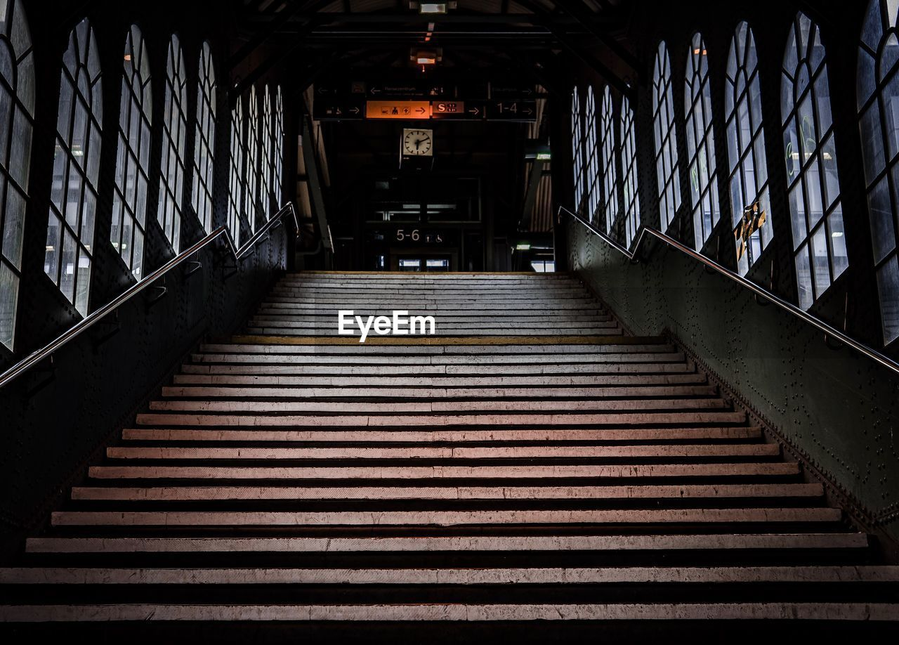 architecture, staircase, railing, direction, the way forward, steps and staircases, built structure, indoors, pattern, empty, no people, transportation, connection, metal, building, high angle view, absence, illuminated, day, ceiling, underpass