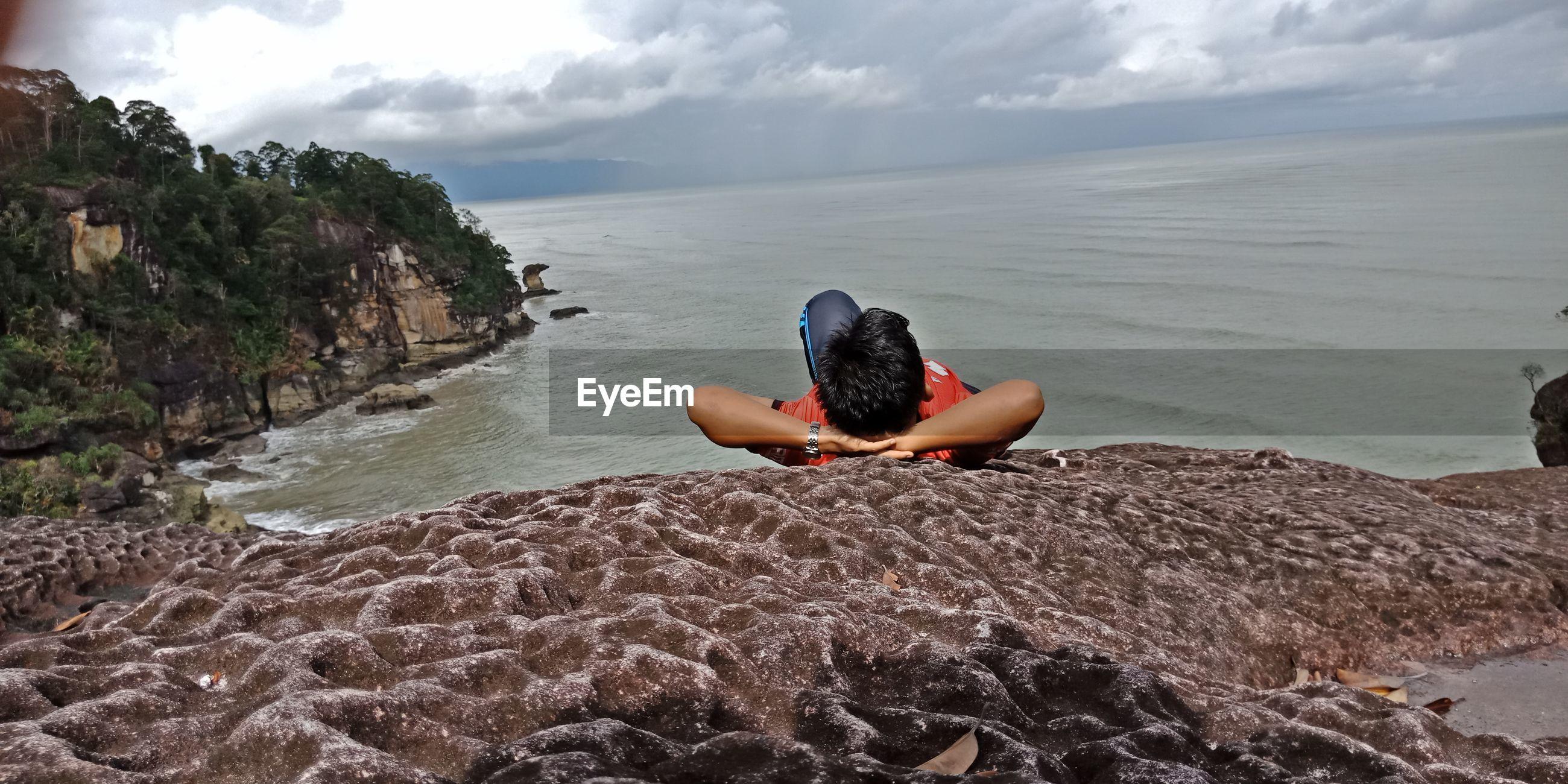 Man lying on cliff against sea
