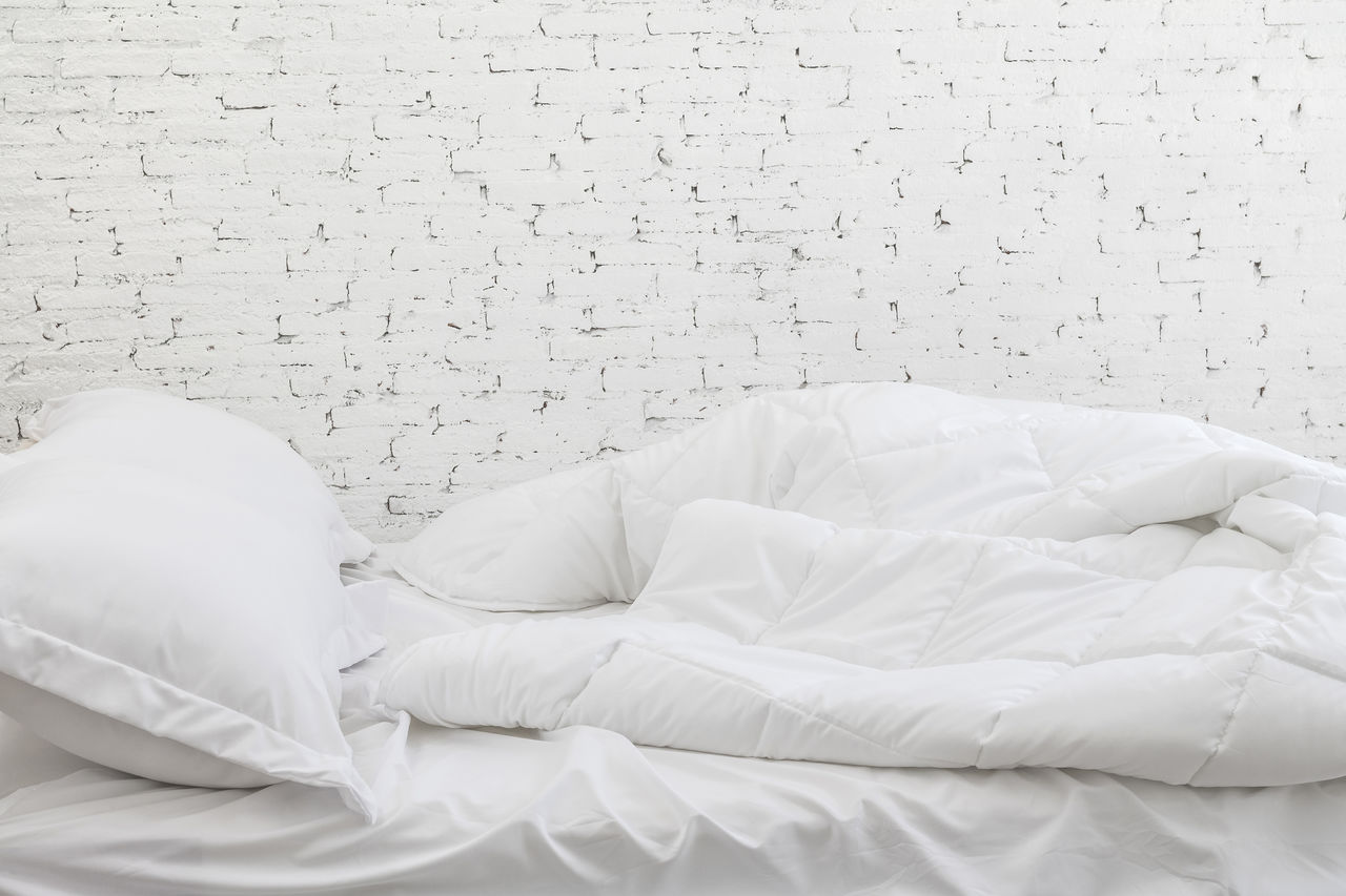 furniture, bed, white color, indoors, pillow, relaxation, no people, bedroom, textile, wall - building feature, domestic room, comfortable, home interior, sheet, linen, clothing, sleeping, absence, pattern, still life, duvet, cozy