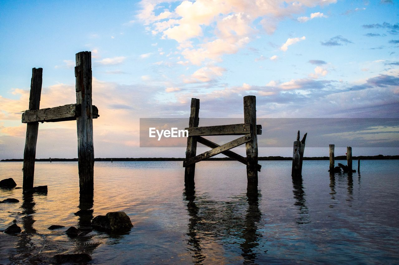 water, sky, wood - material, cloud - sky, post, sea, wooden post, beauty in nature, waterfront, tranquil scene, tranquility, nature, scenics - nature, reflection, no people, pier, architecture, sunset, outdoors