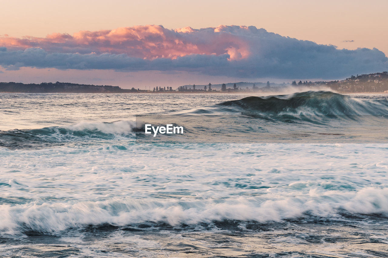 beauty in nature, sea, wave, motion, water, scenics - nature, aquatic sport, sport, waterfront, cloud - sky, surfing, sky, sunset, power, beach, power in nature, rushing, horizon over water, outdoors, flowing water