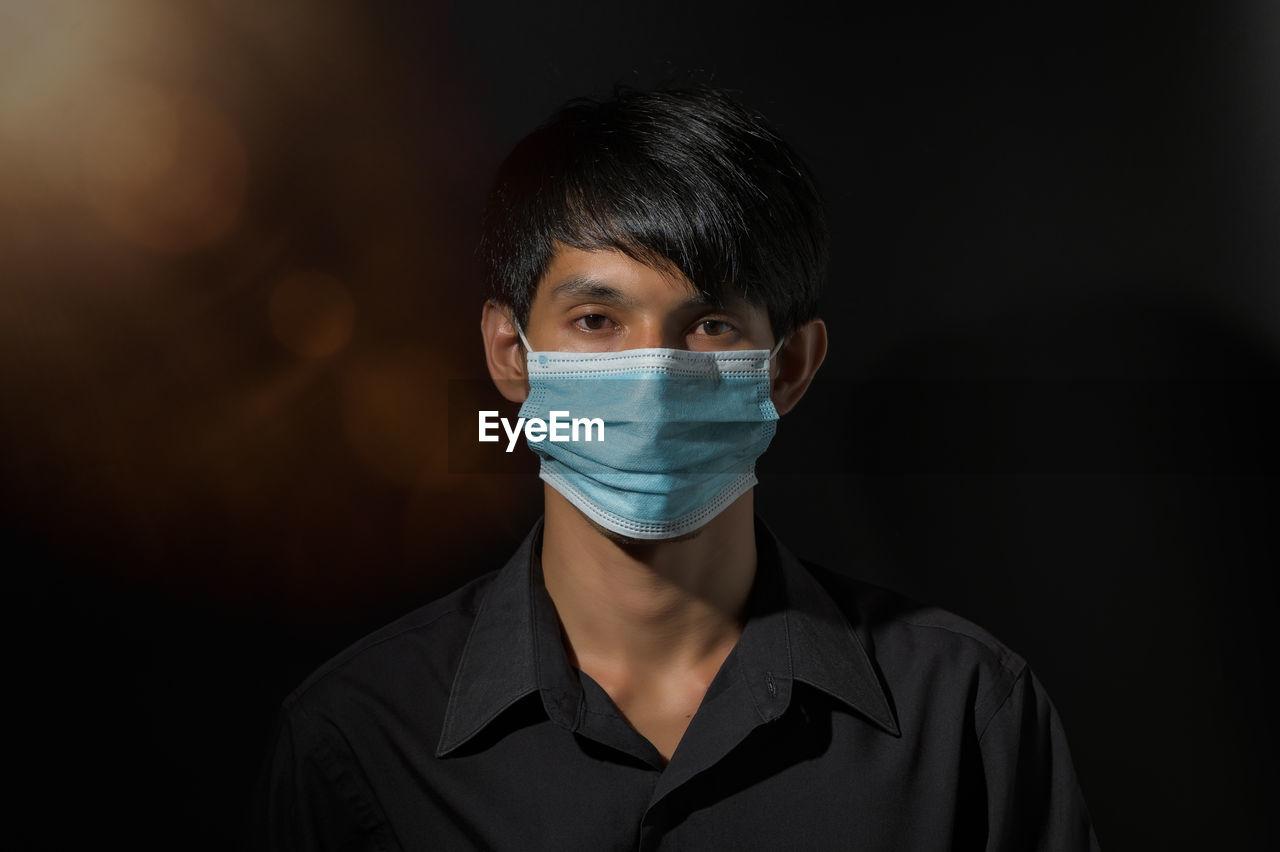 Close-up portrait of man wearing mask against black background