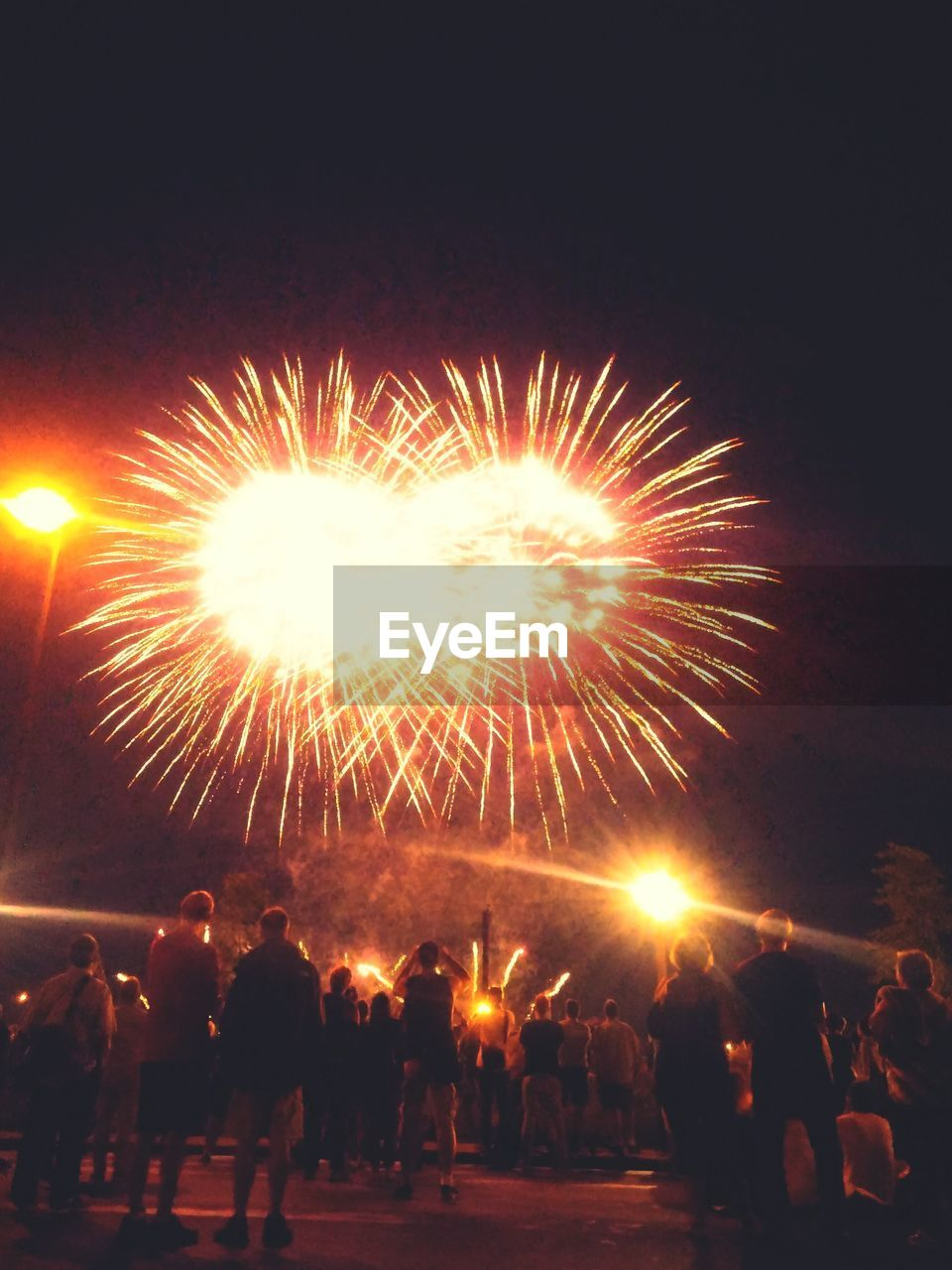 large group of people, real people, firework display, celebration, exploding, firework - man made object, glowing, night, leisure activity, motion, event, men, illuminated, blurred motion, women, lifestyles, long exposure, enjoyment, outdoors, arts culture and entertainment, firework, standing, crowd, sky, people, adult