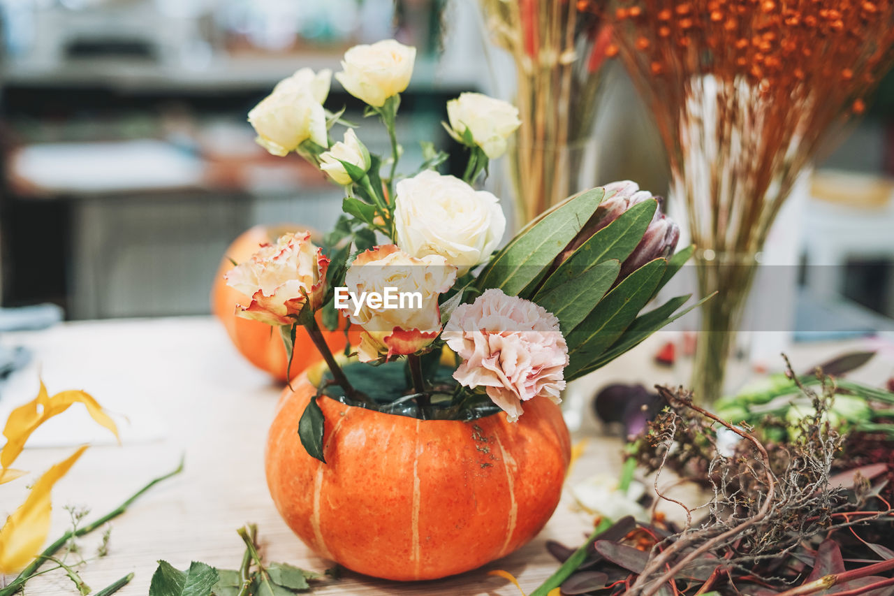 Diy autumn flower arrangement bouquet in pumpkin, florist at work, floristry studio