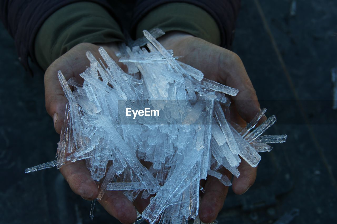 one person, hand, human hand, holding, real people, men, human body part, focus on foreground, midsection, lifestyles, frozen, close-up, day, plastic, leisure activity, narcotic, cold temperature, plastic bag, unrecognizable person, ice, outdoors
