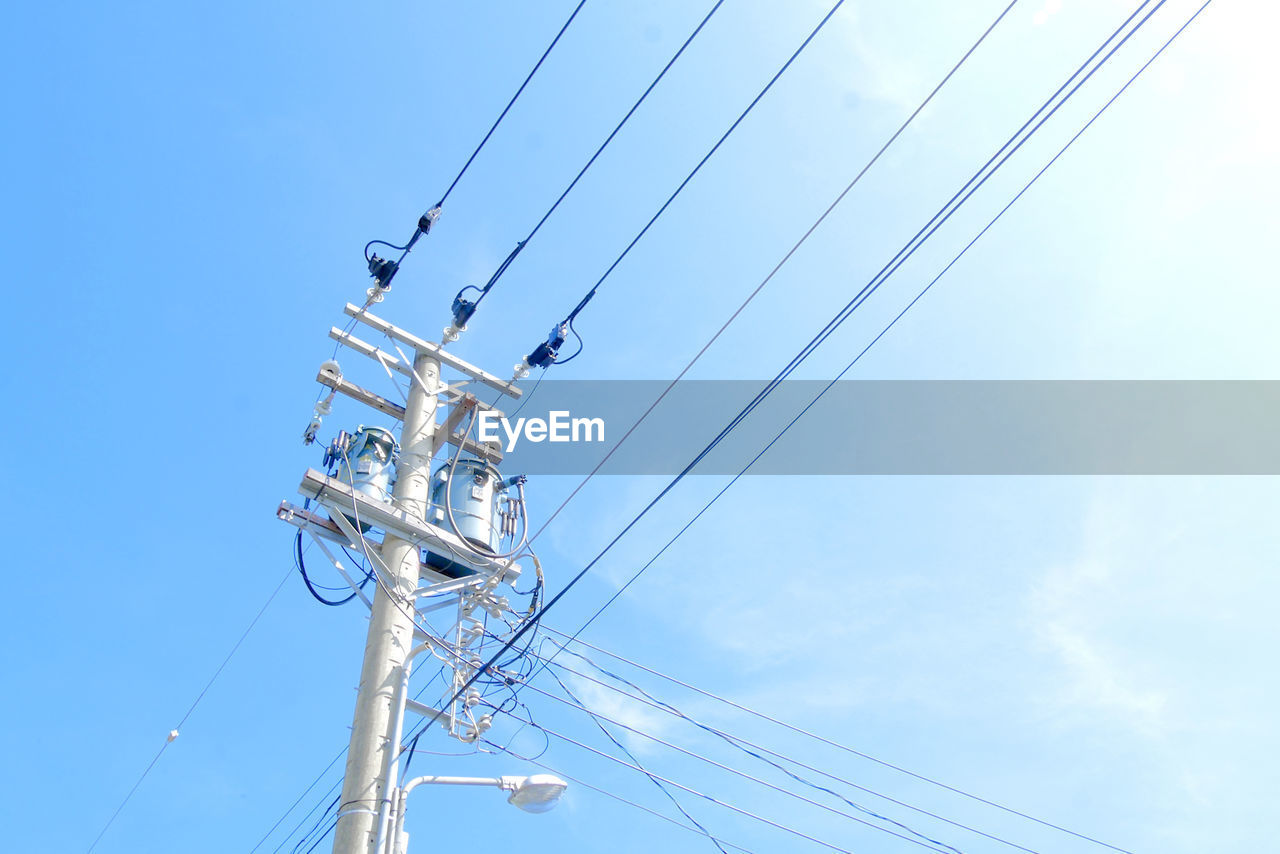 sky, low angle view, cable, blue, electricity, technology, connection, day, cloud - sky, nature, power line, no people, power supply, built structure, outdoors, complexity, sunlight, architecture, tower, fuel and power generation