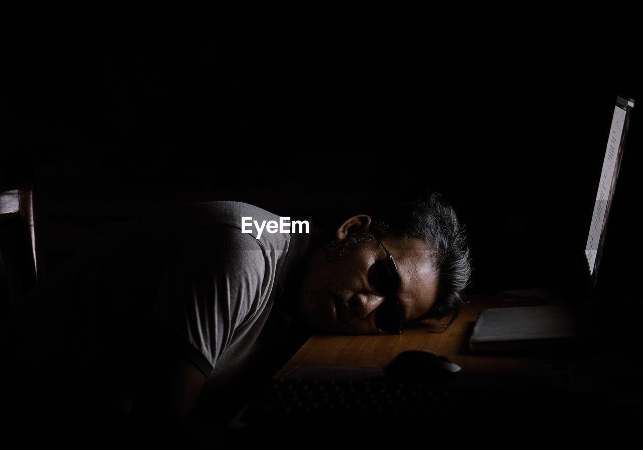 Man sleeping on desk by laptop in darkroom
