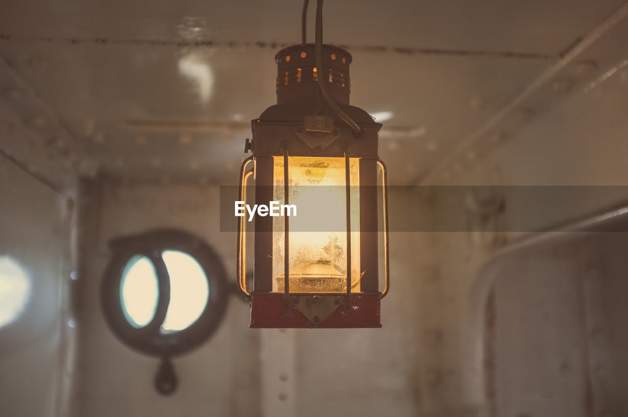 Illuminated lamp hanging in boat