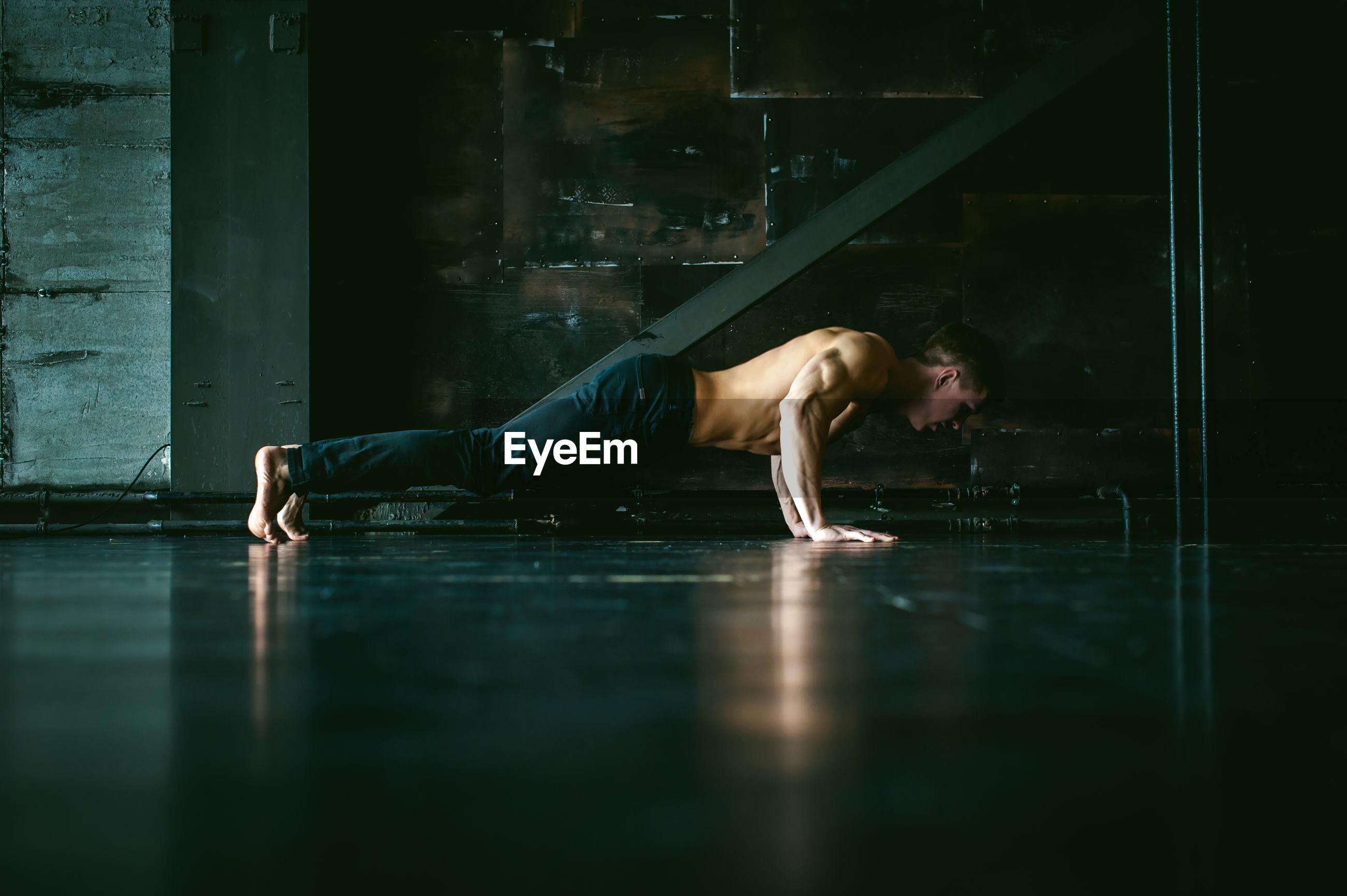 Shirtless muscular man practicing push-ups on floor