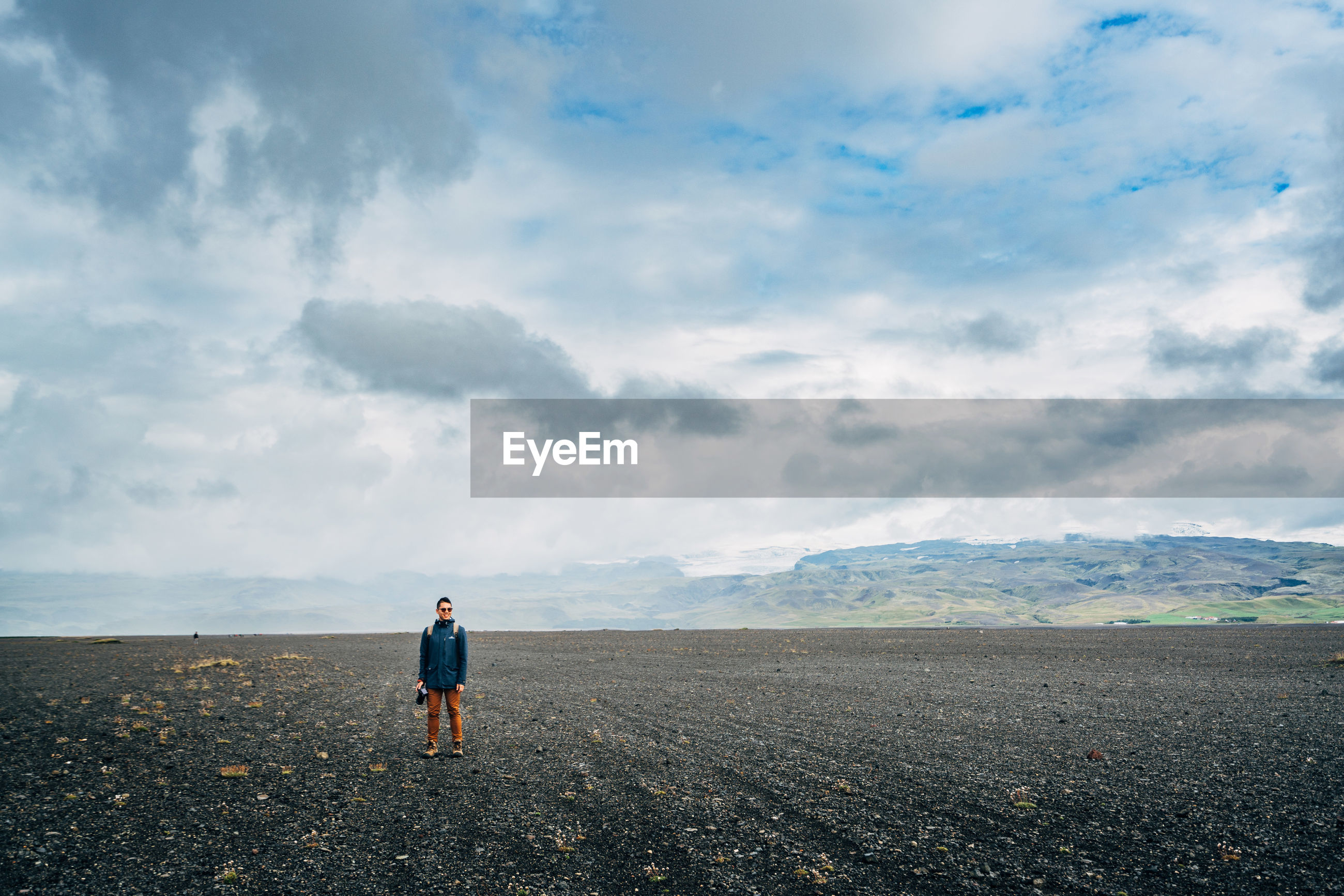 Man with camera standing on field against cloudy sky