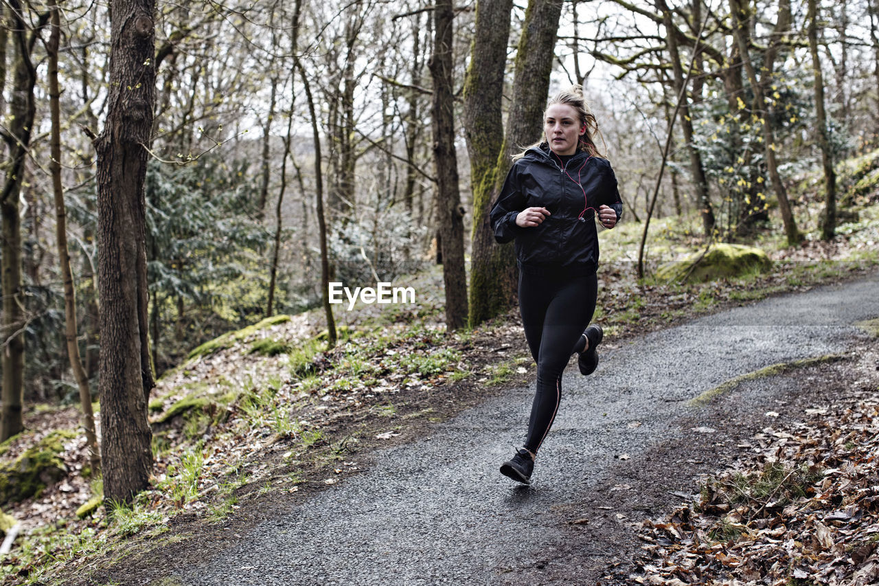 tree, forest, land, one person, running, plant, full length, lifestyles, nature, adult, young adult, jogging, exercising, clothing, footpath, real people, front view, woodland, day, outdoors