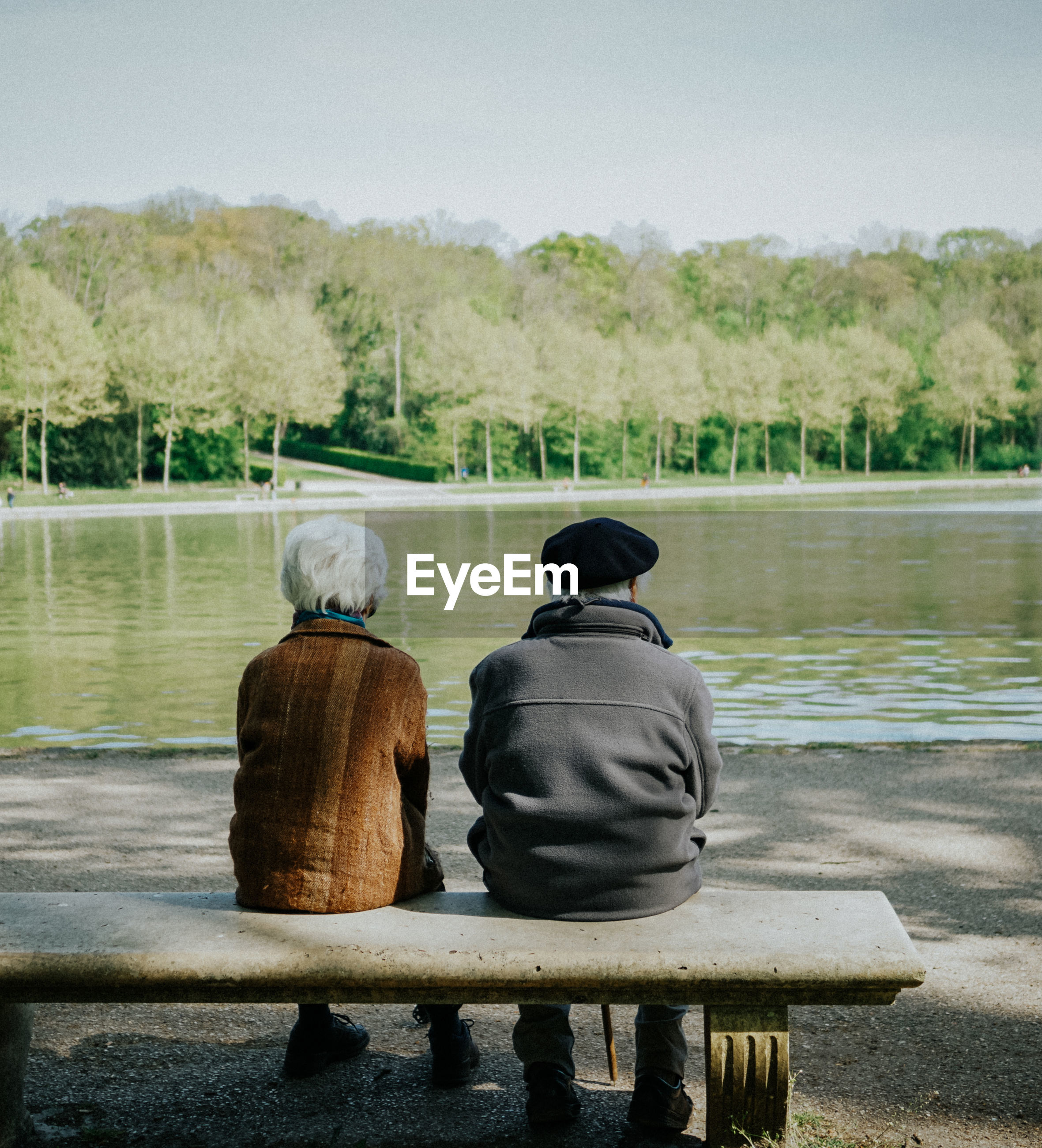 Rear view of couple sitting at lakeshore against sky