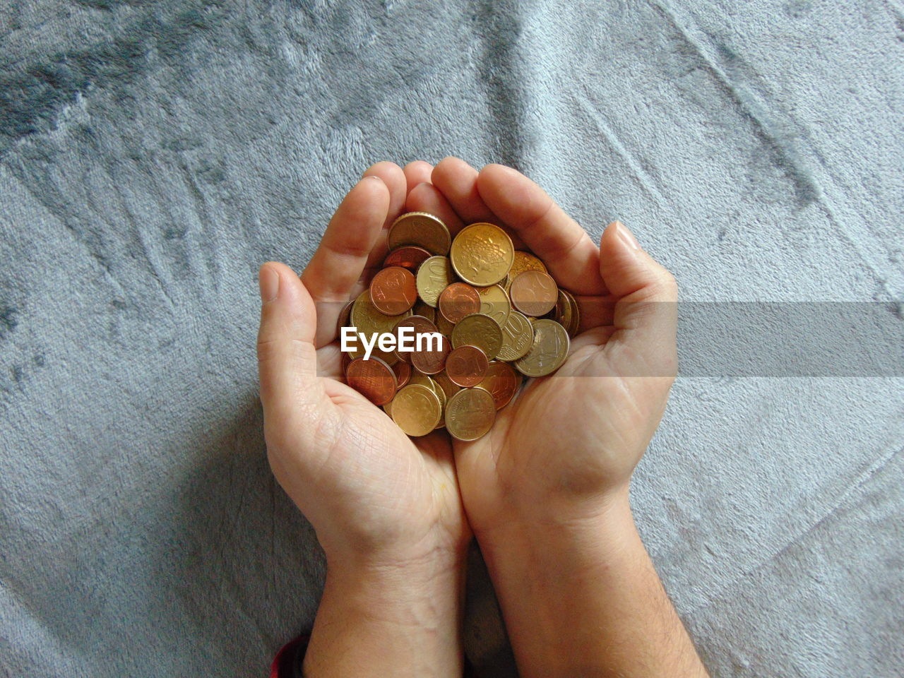 High Angle View Of Man Holding Coins Over Gray Fabric