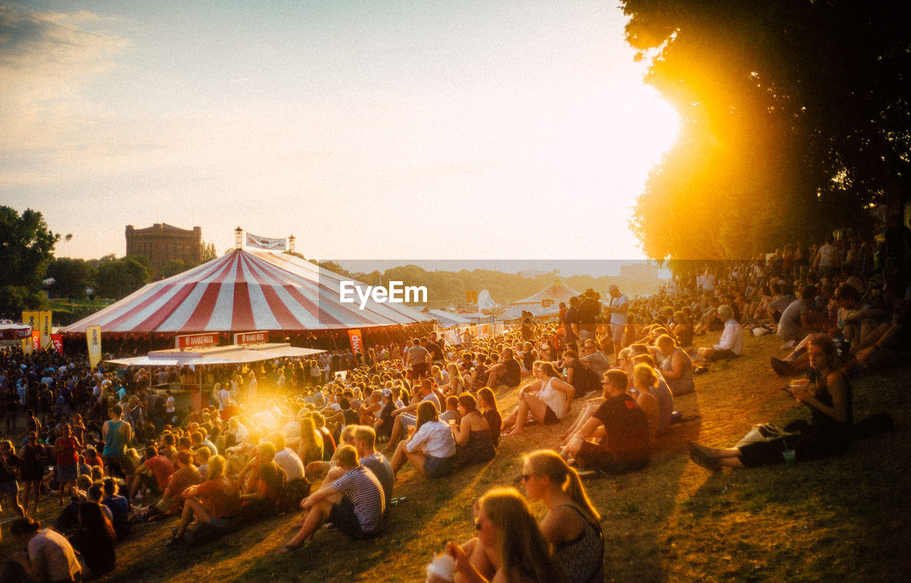 crowd, large group of people, group of people, real people, sky, nature, women, event, men, leisure activity, lifestyles, outdoors, illuminated, sunset, sunlight, land, architecture, plant, tree, festival, music festival