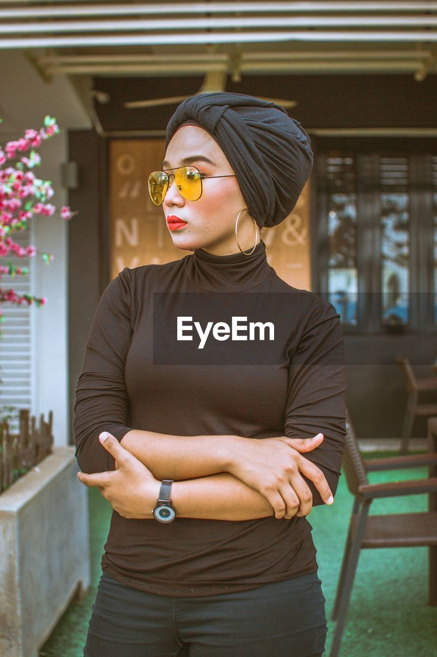one person, standing, glasses, fashion, young adult, sunglasses, three quarter length, lifestyles, front view, real people, focus on foreground, young women, adult, leisure activity, casual clothing, day, women, looking away, beautiful woman, outdoors, hairstyle, contemplation