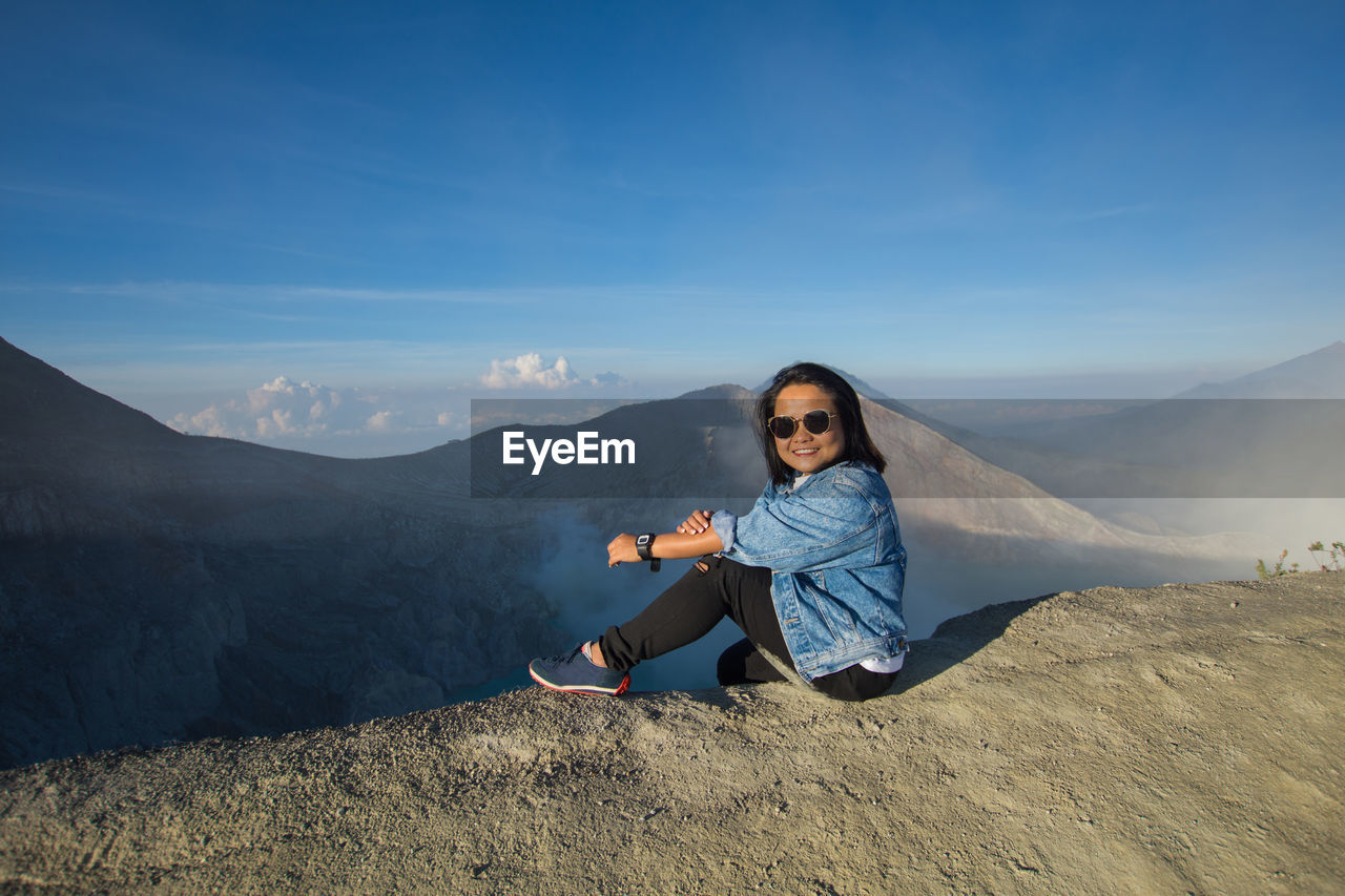 Side View Full Length Of Woman Sitting On Mountain