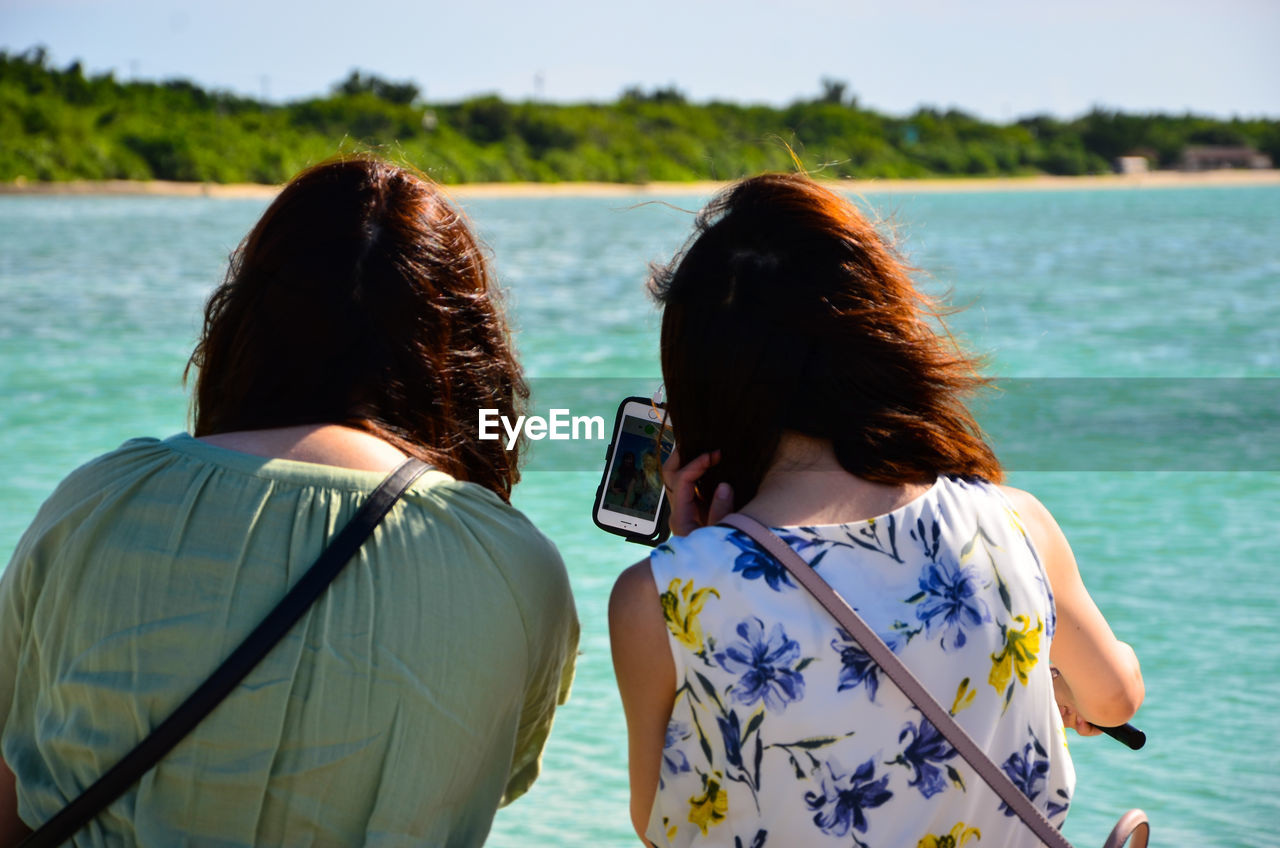 Rear View Of Friends Looking At Smart Phone By Sea