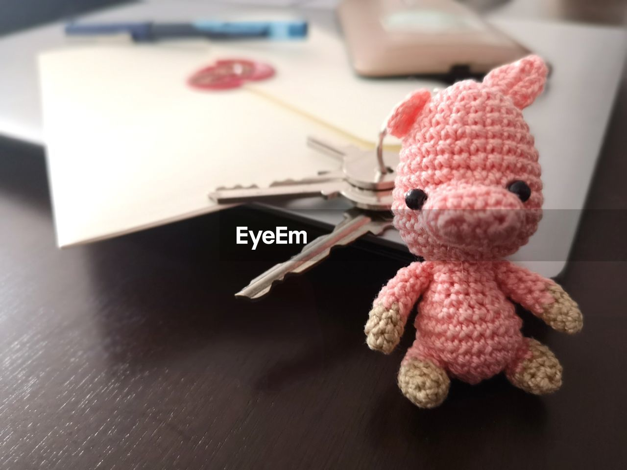 Close-up of woolen toy with papers and keys on table