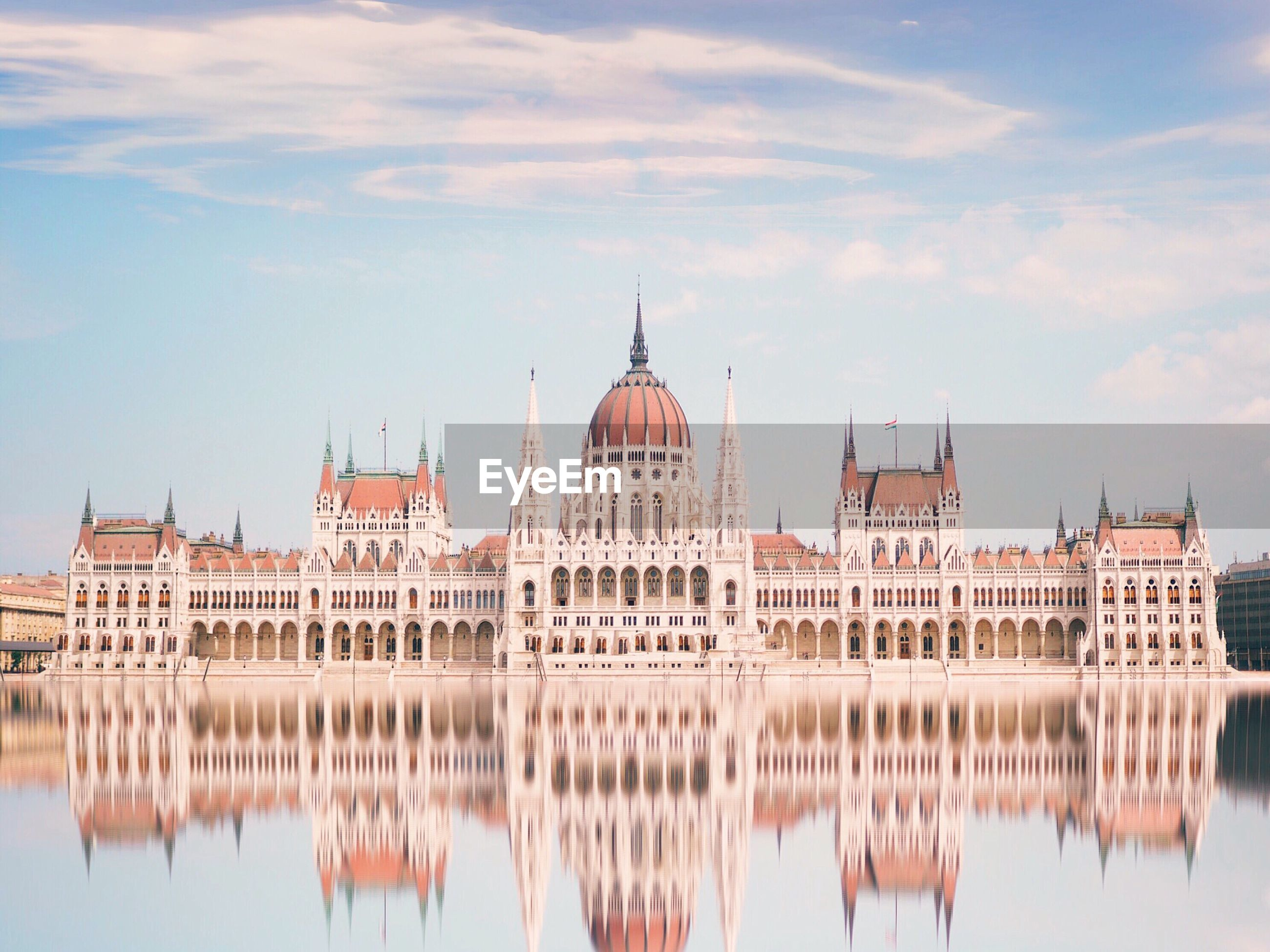 Reflection of hungarian parliament building in river against sky