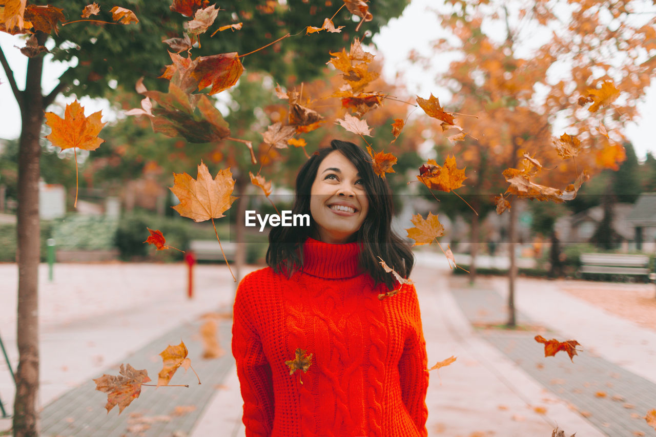 Smiling Woman Looking At Leaves While Standing On Footpath During Autumn
