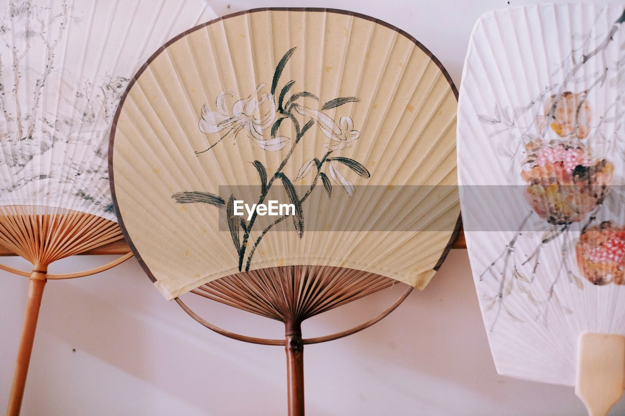 indoors, table, no people, decoration, still life, art and craft, floral pattern, close-up, pattern, design, high angle view, creativity, white color, plant, craft, nature, wall - building feature, wood - material, flower, foldable