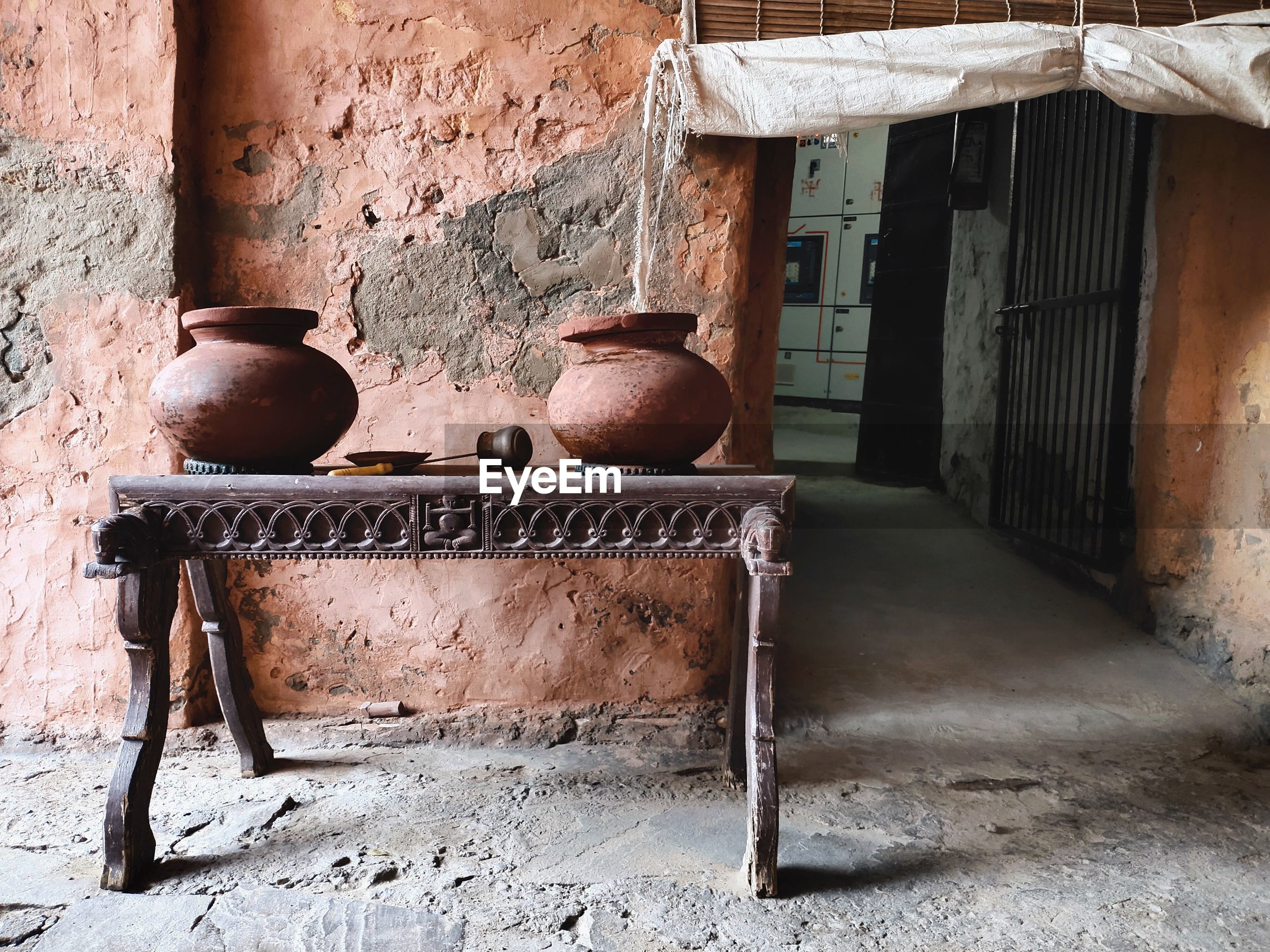 Street journals- earthenware water pots by the old weathered wall