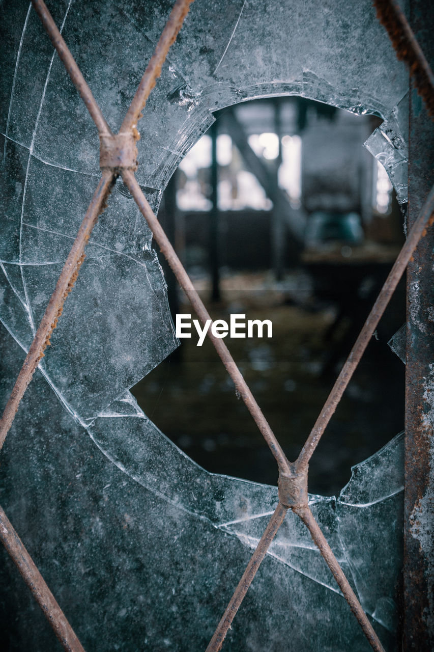 architecture, built structure, no people, metal, close-up, window, focus on foreground, fence, broken, day, boundary, damaged, security, abandoned, barrier, outdoors, nature, safety, glass - material, protection