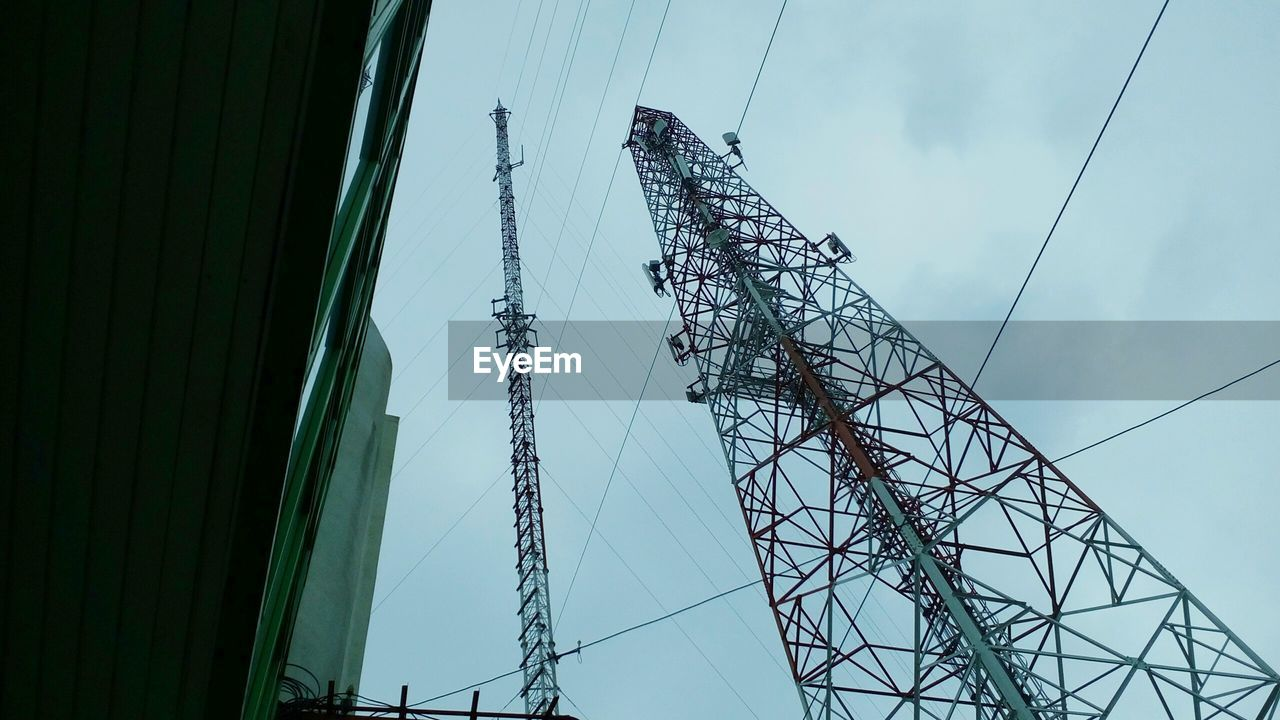 Low angle view of communications towers and building against cloudy sky
