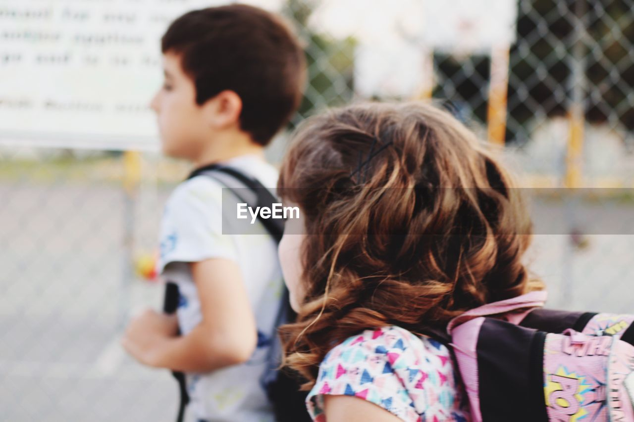 Side view of siblings with backpack