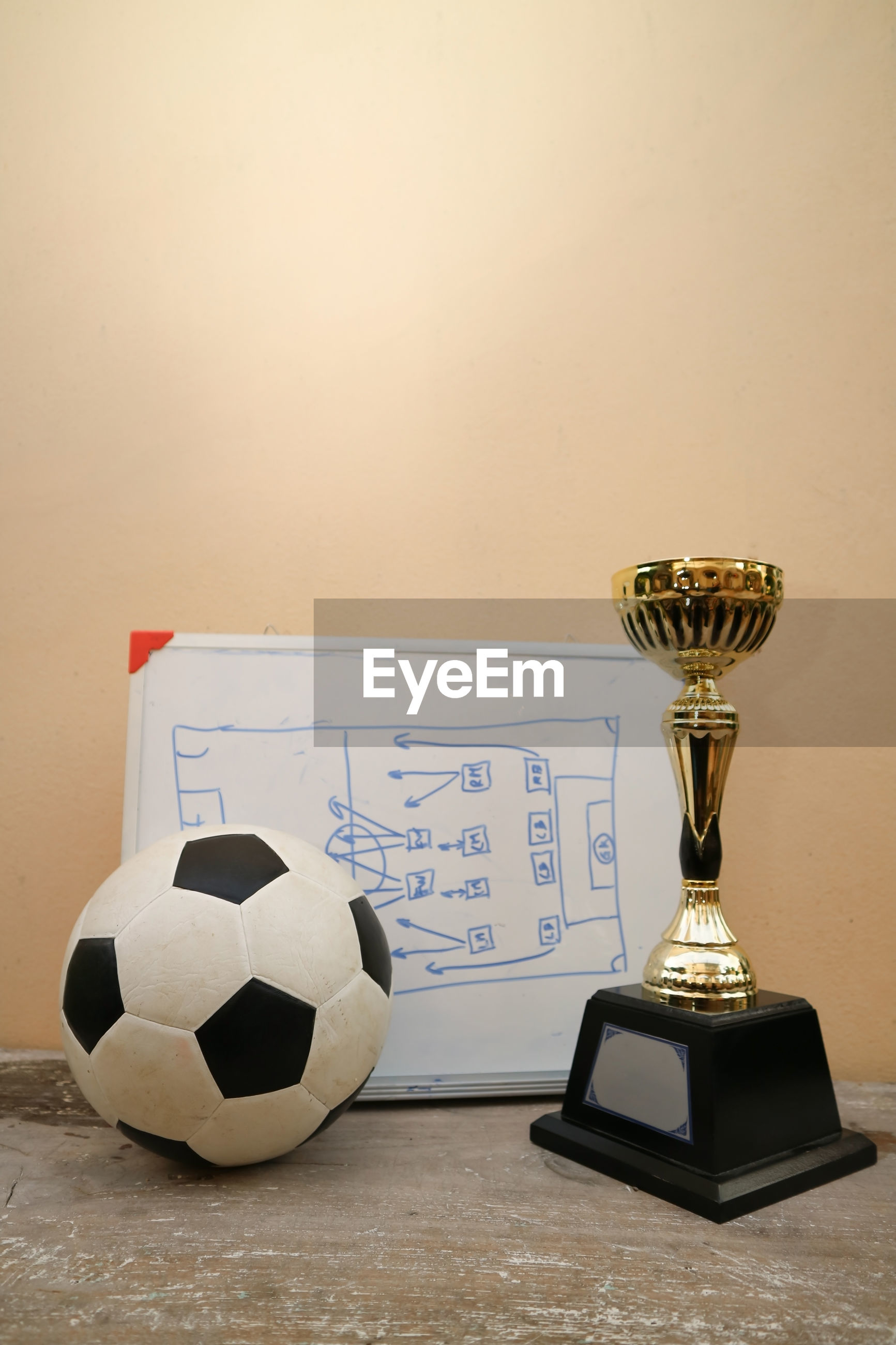 Close-up of soccer ball with award and whiteboard on table
